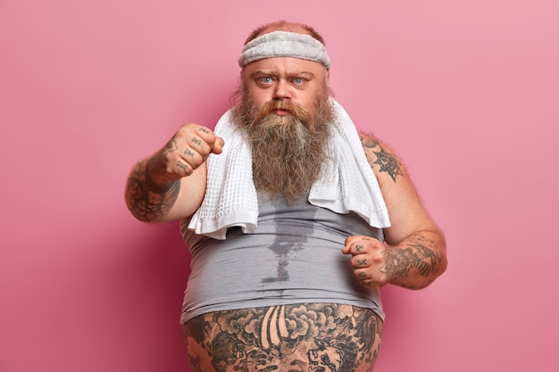 真面目なぽっちゃりしたあごひげを生やした男は、握りこぶしを見せ、余分な体重に苦しみ、スポーツに出かけ、汗をかいた体と入れ墨のある腕を持ち、ピンクの壁に向かってポーズをとります。痩身とダイエットのコンセプト。