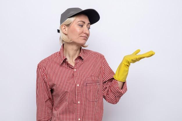 何かを提示している彼女の腕を見ているゴム手袋を着用している格子縞のシャツとキャップの深刻な掃除の女性