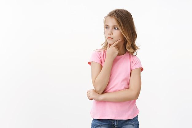 금발 머리를 가진 진지하고 영리한 어린 소녀, 무엇을 그리는지 생각하는 딸, 영감을 찾고, 턱을 사려 깊게 만지고, 결정을 숙고하고, 호기심이 많은 표정을 짓고, 무엇을 살지, 흰 벽에 서다