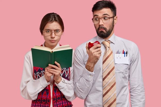 Studentessa intelligente seria con occhiali lenti spesse tiene il manuale, studia al coperto, uomo barbuto sorpreso in camicia formale