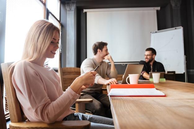 深刻な同僚がオフィスに座ってノートパソコンと電話を使用している