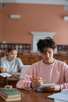 Серьезный студент колледжа в наушниках слушает музыку во время чтения заметок в блокноте