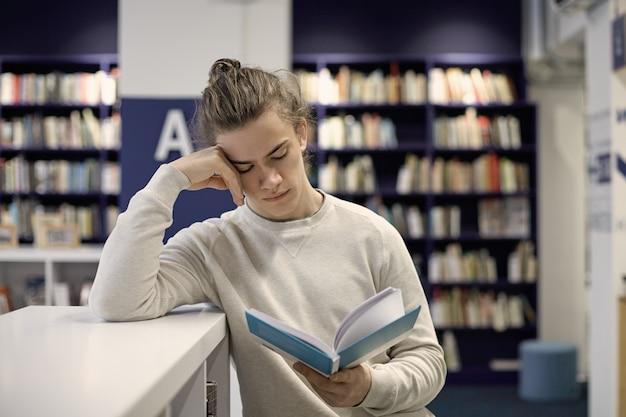 Серьезный студент колледжа с пучком волос, поглощенный учебником, ищущий информацию для образовательных исследований, сосредоточил и сконцентрировал выражение на своем чисто выбритом лице