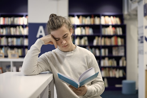 Serious college student with hair bun absorbed in textbook, looking for information for educational research, having focused and concentrated expression on his clean shaven face