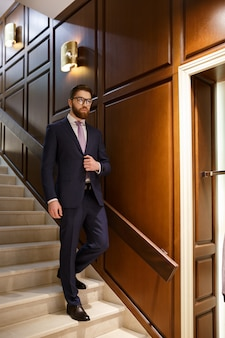 Serious concentrated bearded young businessman on ladder