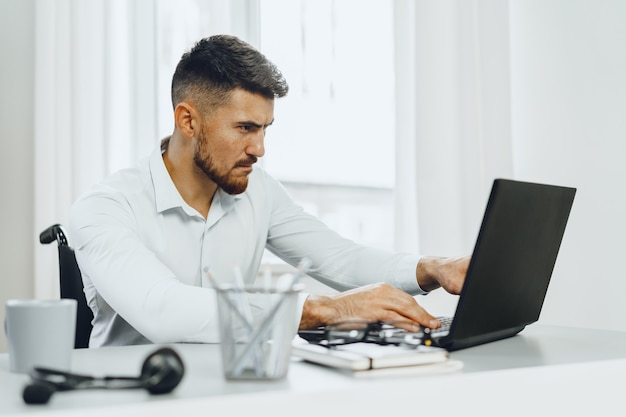 Serious concentrated disabled man in wheelchair using his laptop for work seeking a job in internet