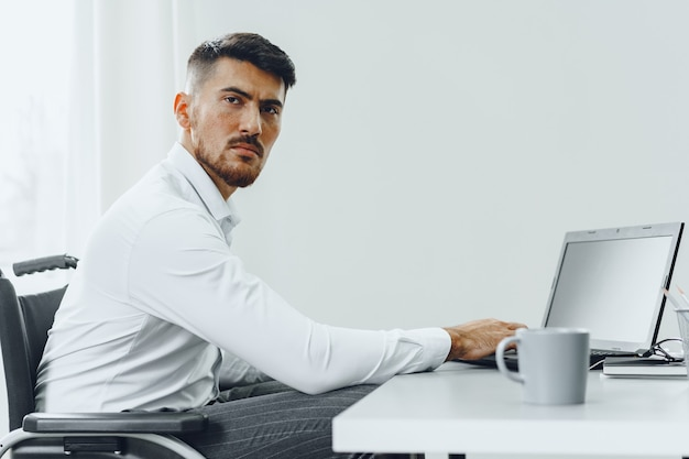 Serious concentrated disabled man in wheelchair using his laptop