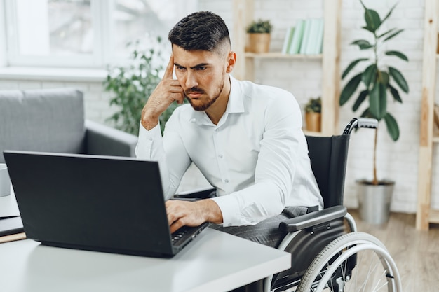 Serious concentrated disabledman in wheelchair using his laptop for work / seeking a job in internet