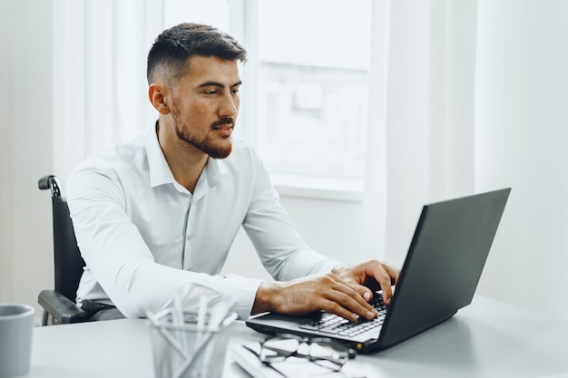 Serious concentrated disabledman in wheelchair using his laptop