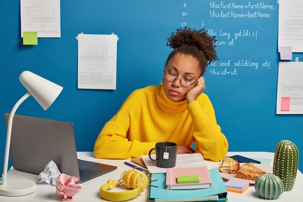 Serious concentrated female student uses online education service, watches training webinar or course on laptop, has many things on table, drinks tea