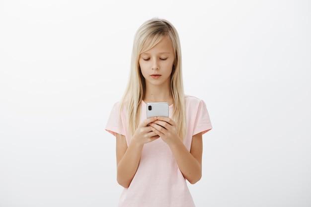 大人っぽく振る舞うまじめな女の子。ブロンドの髪、スマートフォンを押しながら画面を見たり、漫画を見たり、灰色の壁越しにメッセージを送ったりして焦点を合わせた愛らしい子供の屋内撮影