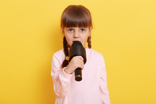 Serious and concentrated little girl singing or talking in microphone isolated on yellow wall, child with pigtails performing, , dresses casually.