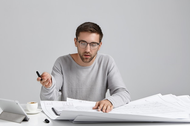 Serious concentrated male designer wears loose sweater and round glasses, looks attentively at sketches