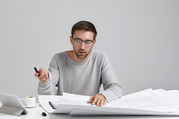 Un designer maschio serio e concentrato indossa un maglione ampio e occhiali rotondi, guarda attentamente gli schizzi