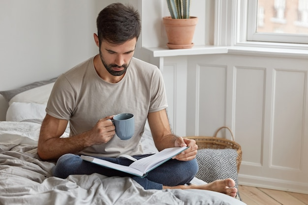 Serious concentrated male reads book during day off, involved in reading, drinks hot beverage, sits crossed legs on bed, wears casual t shirt and trousers. people, knowledge, education, leisure