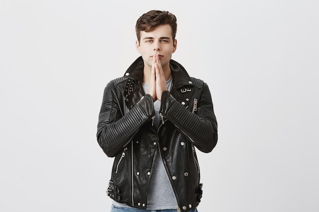 Serious concentrated man in black leather jacket keeps palms together, prays for well being of family, hopes for better, has strong belief. male student worries about his future, asks for good luck