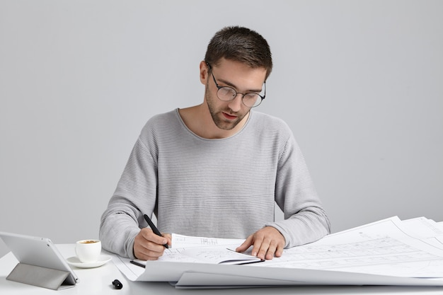 Serious concentrated man draws sketches, prepares blueprint, uses modern tablet