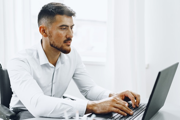 Serious concentrated man in wheelchair using his laptop for work