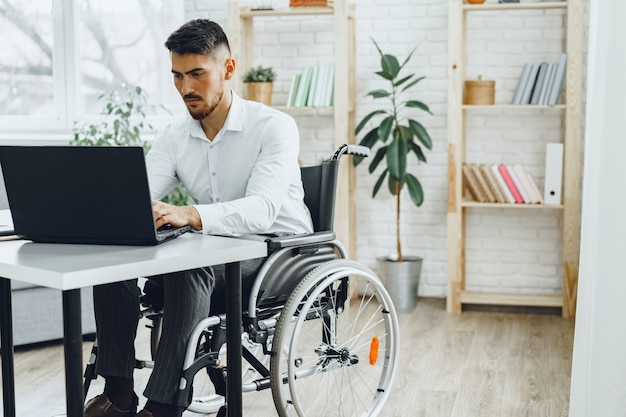Serious concentrated man in wheelchair using his laptop
