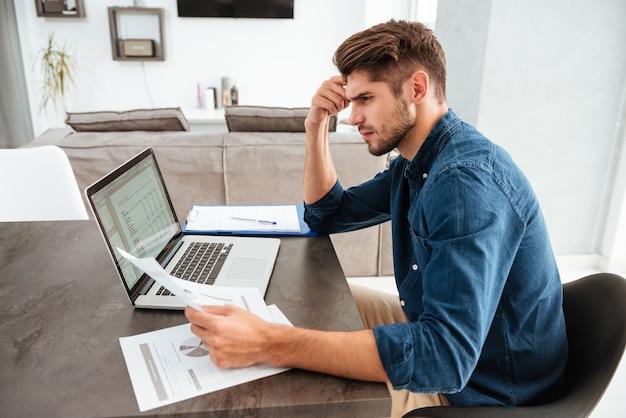 Серьезный сконцентрированный человек, работающий за ноутбуком и сидящий за столом, глядя на документы и держась за голову рукой