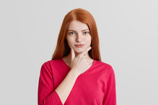 Serious concentrated redhead female with freckled face, keeps hands under chin, looks confidently into camera, wears red turtleneck sweater, isolated over white wall. facial expressions concept