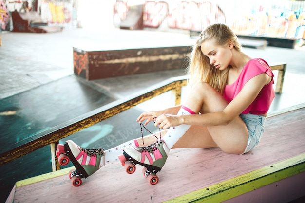 Serious and concentrated rollerblader is sitting and tying laces on rollers