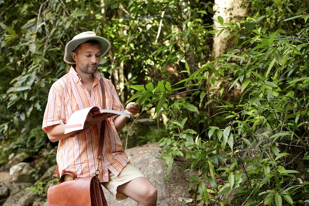 Serious and concentrated scientist with leather bag and manual in his hand reading information about exotic plant while exploring bio-diversity in rainforest,.