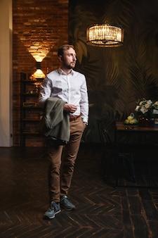 Серьезный сосредоточенный мужчина в рубашке, держащий в руке куртку, стоит в современной квартире-лофте
