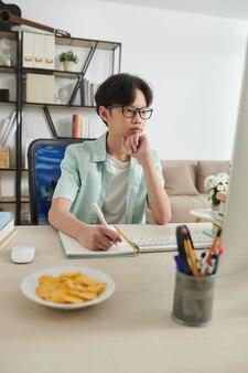 안경을 쓴 진지하게 집중된 10대 소년이 웹 세미나를 보거나 컴퓨터로 기사를 읽고 집에서 교과서에 글을 씁니다.