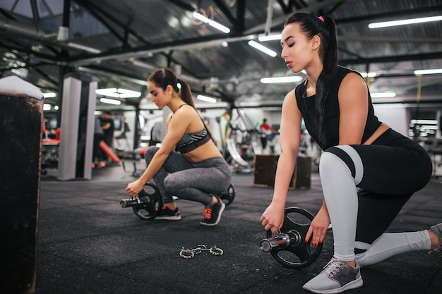Serious an concentrated young asian woman stand on one knee and look down. she put some weight to barbell. her european friend repeat actions after her. they are in gym.