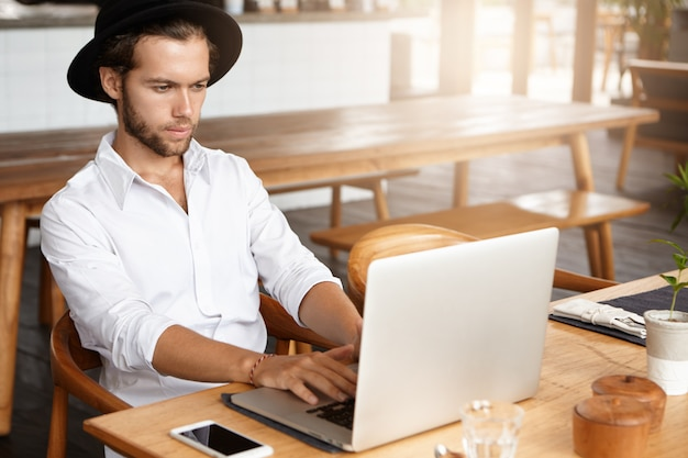 Serious and concentrated young bearded freelancer wearing stylish hat and white shirt using laptop computer for remote work, sitting at cafe table with notebook pc and blank screen mobile phone