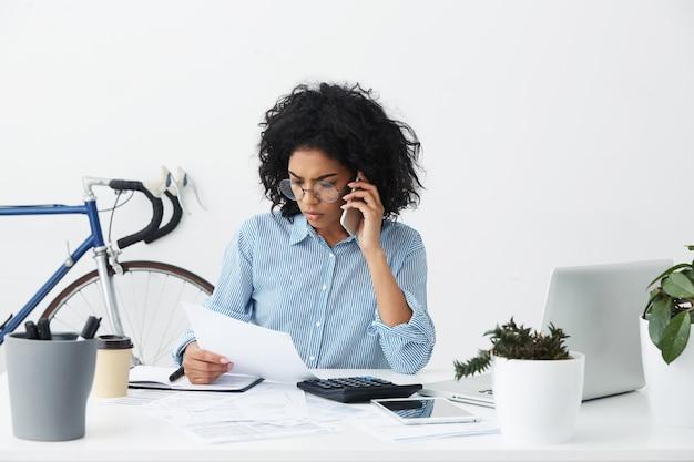 Серьезная сконцентрированная молодая женщина-предприниматель разговаривает по мобильному телефону