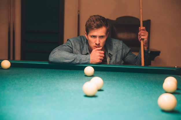 Serious and concentrated young man thinking. he look at billiard balls on bed of table. guy hold billiard cue. he is alone in room.