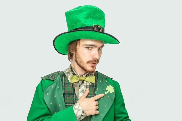 Серьезный сосредоточенный молодой человек читал точку на клевер на костюме. он носит зеленую одежду и шляпу. парень смотри. изолированные на сером.