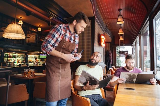 Серьезный сосредоточенный молодой официант стоит и принимает заказ от двух бородатых красавцев в кафе