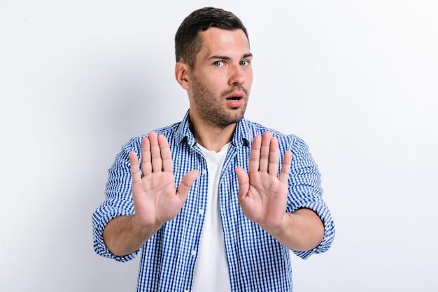 손바닥을 보여주는 중지 제스처, 위험에 대한 충돌 금지 경고, 왕따를 중지하는 수염을 가진 심각한 우려 남자. 흰색 배경에 고립 된 실내 스튜디오 촬영
