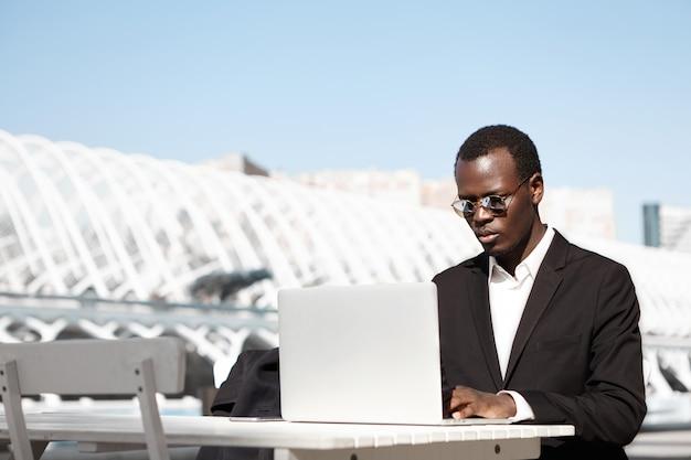丸い色合いとフォーマルなスーツを着た真面目で自信のある黒人起業家が集中した表情で彼の前のラップトップの画面を見て、ビジネスパートナーがアーバンカフェでの会議を待っている