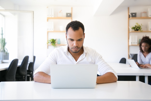 Serious confident businessman using laptop in office