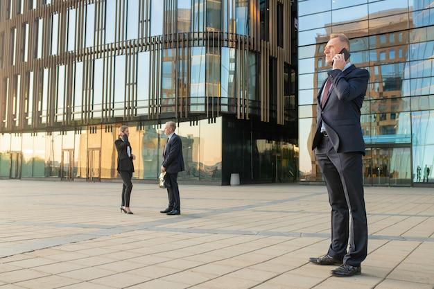 屋外で携帯電話で話しているオフィススーツを着て真面目な自信の実業家。ビジネスマンおよび都市の背景にガラスのファサードを構築します。スペースをコピーします。ビジネスコミュニケーションの概念
