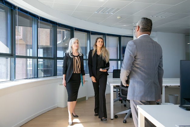 Serious confident businesswomen walking to man in suit in office interior. full length, back view. business meeting concept