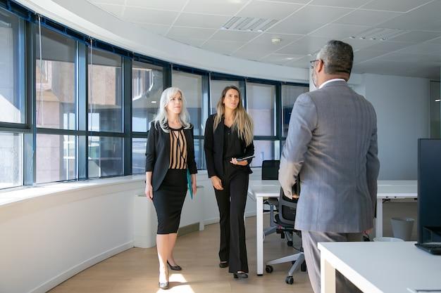 Серьезные уверенно бизнесмены, идущие к человеку в костюме в интерьере офиса. полная длина, вид сзади. концепция деловой встречи