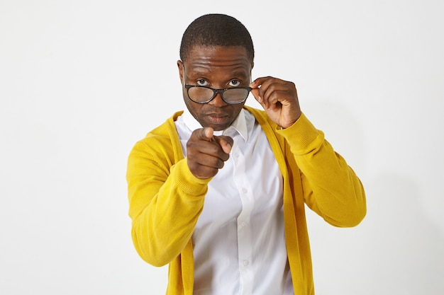 Serious confident dark skinned male teacher in eyewear pointing index finger , having strict look, warning his students, standing isolated at white  wall with copyspace for your text