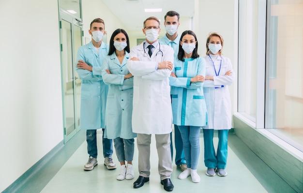 Команда серьезных уверенных врачей в защитных медицинских масках со скрещенными руками смотрит в камеру на фоне больницы