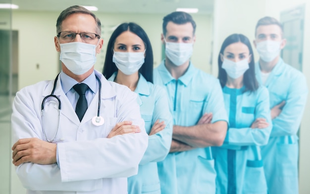 腕を組んで安全医療マスクの深刻な自信を持っている医師チームが病院の背景にカメラを見ています