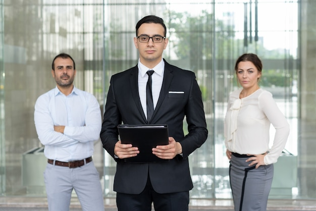 Serious confident entrepreneur standing in front of colleagues