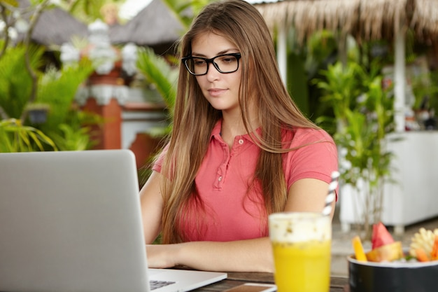 Serious and confident female freelancer wearing rectangular glasses using laptop for remote work during vacations, sitting at summer cafe during breakfast, having healthy fruit cocktail.