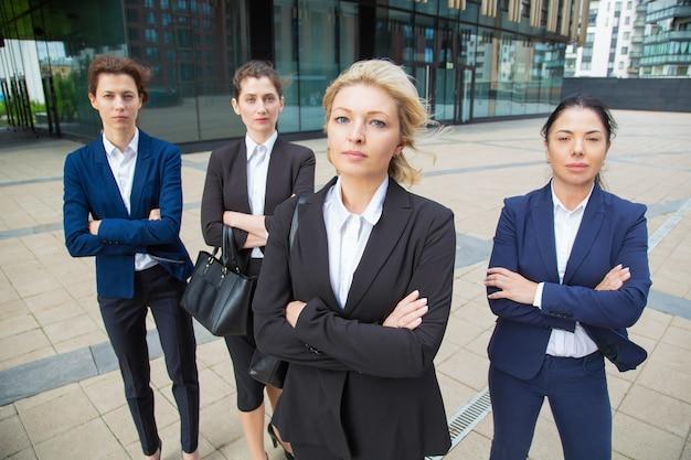 深刻な自信を持って女性のプロのチームが一緒に事務所ビルの近くのグループリーダーと一緒に立って、ポーズをとって、カメラ目線します。正面図。ビジネスウーマングループの肖像画のコンセプト