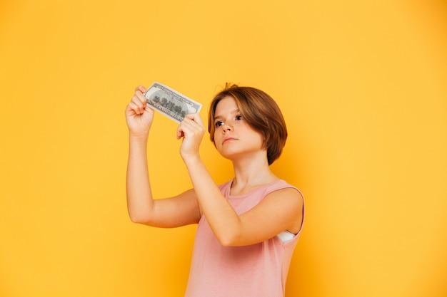 Ragazza sicura seria che esamina banconota e che la controlla isolata