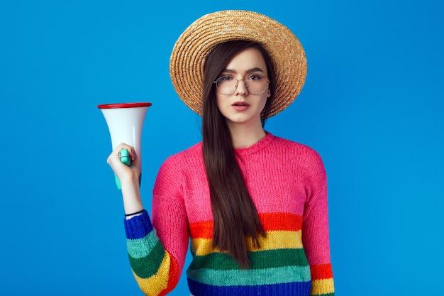 Серьезная уверенная в себе девушка-активистка лгбт в радужном свитере с мегафоном
