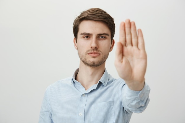 Serious confident man extend hand to shop stop, warning or restriction